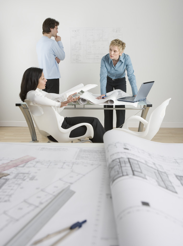 Architectural Team Going over Blueprints --- Image by © Royalty-Free/Corbis